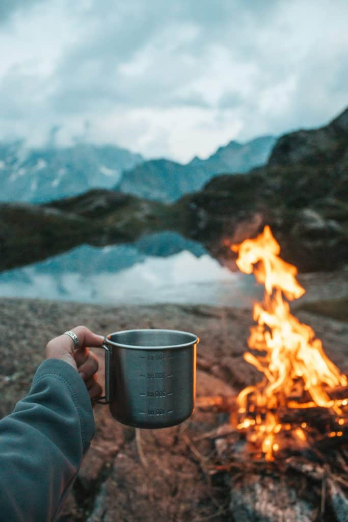 siting by the camp fire with coffee cup