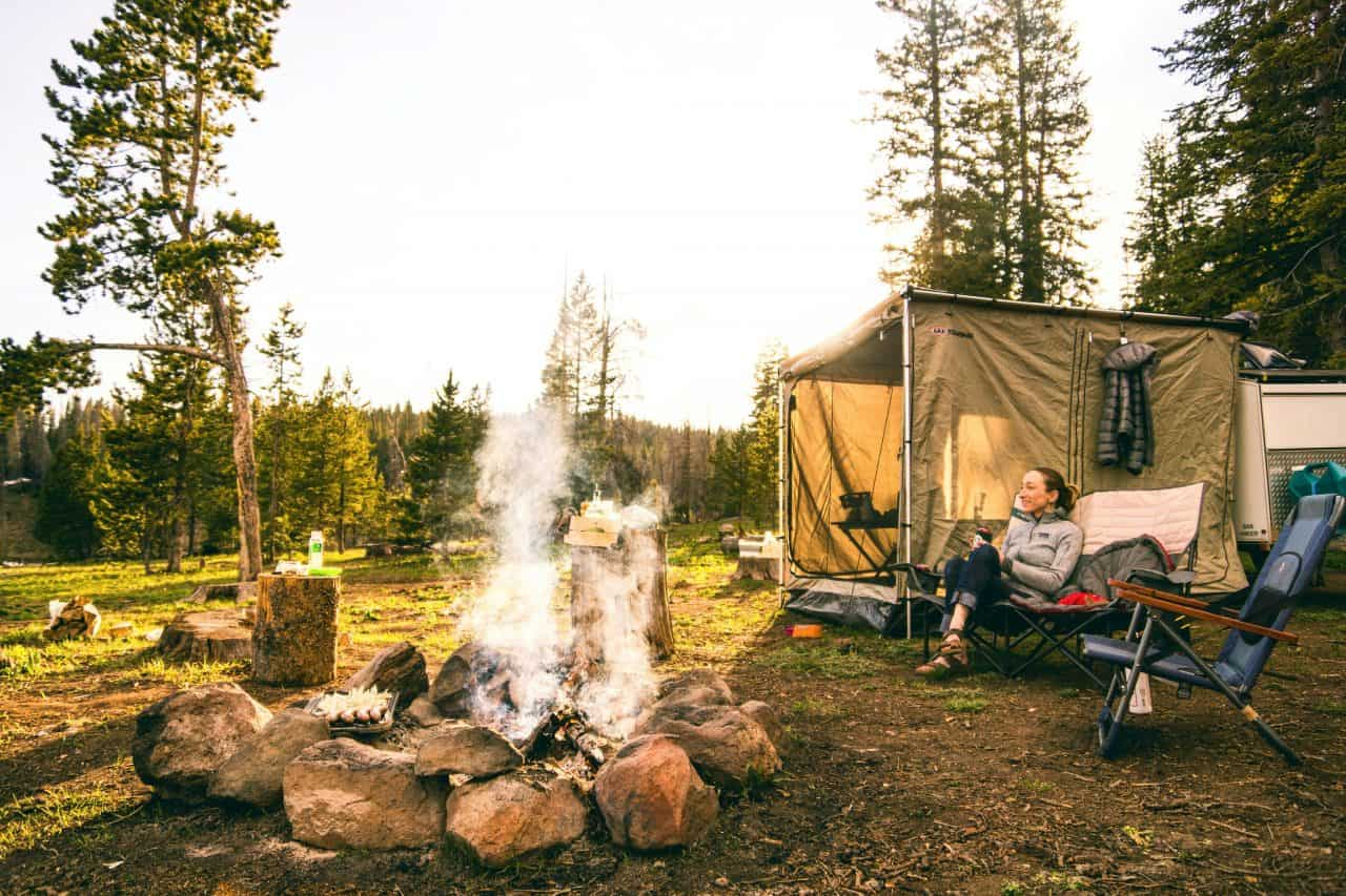 woman relaxing in a chair near the camp fire