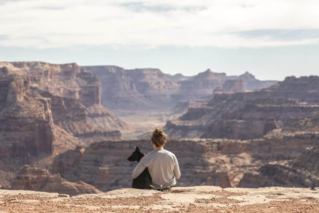 woman holding dog by canyon