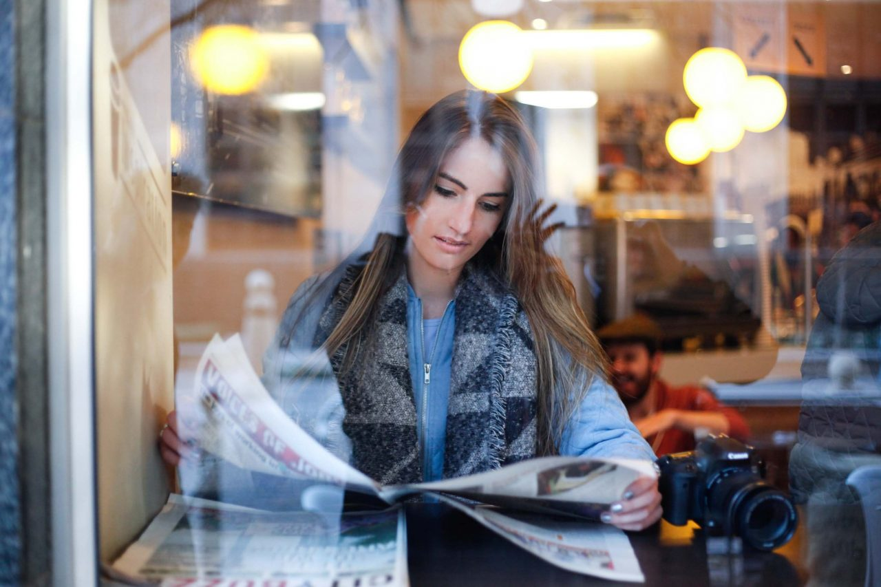 woman reading newspaper in a cafe in the morning