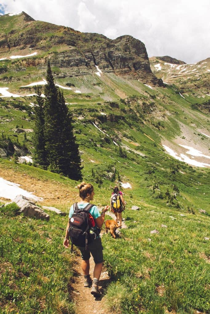 2 women and a dog hiking down a mountain