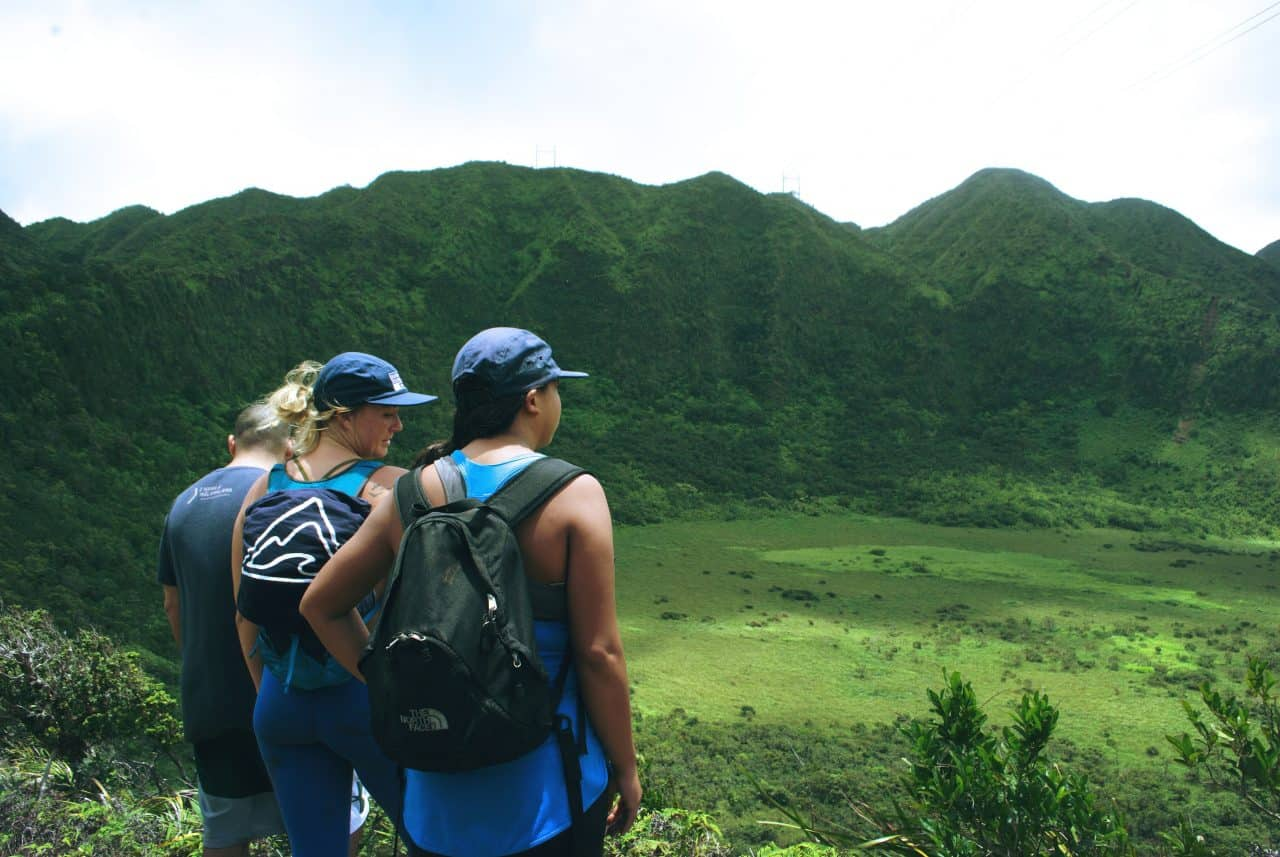 people looking over a tropical valley during a hike