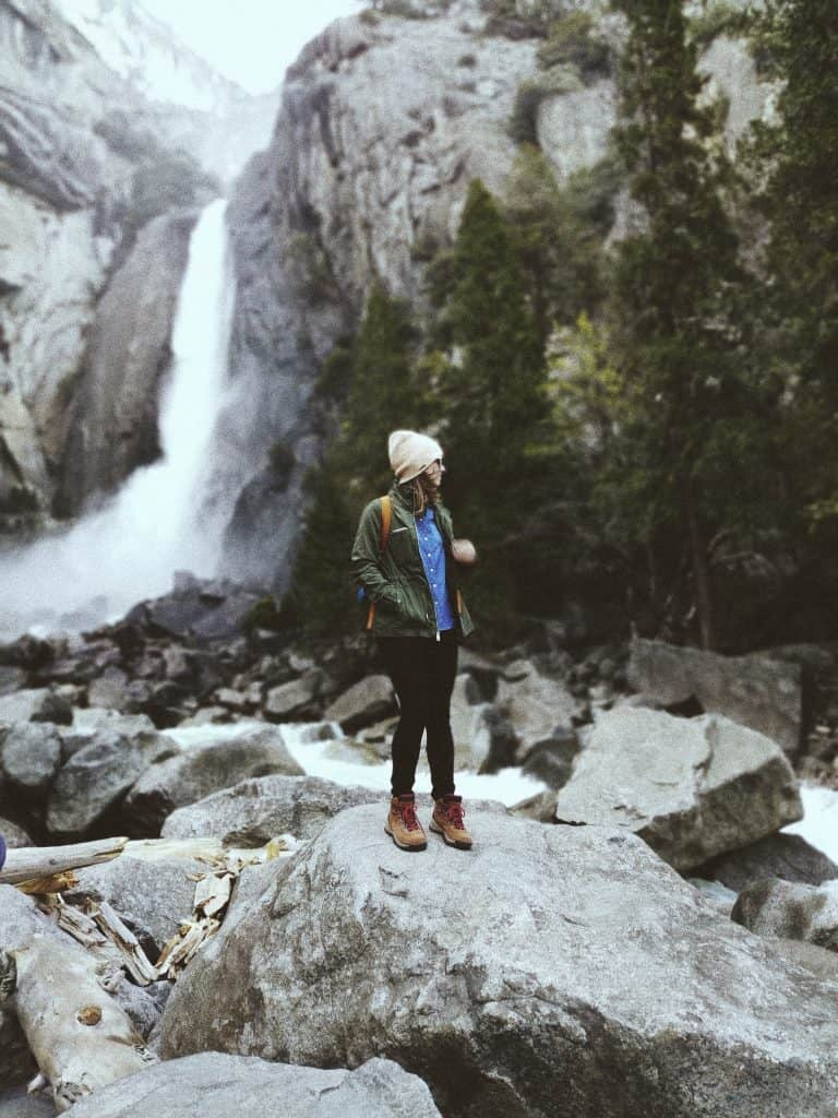 women with hiking clothes on in front of waterfall