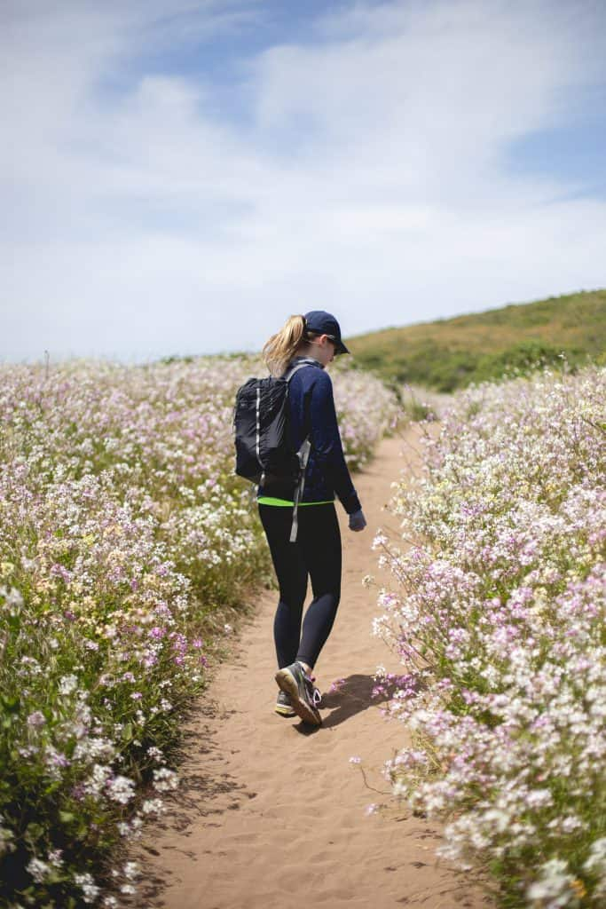 girl walking along flowered covered path