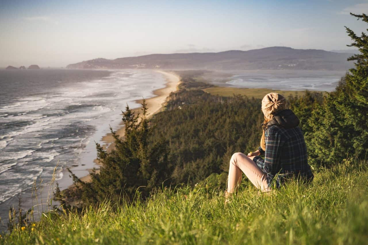 girl relaxing on a grass covered hill overlooking the ocean