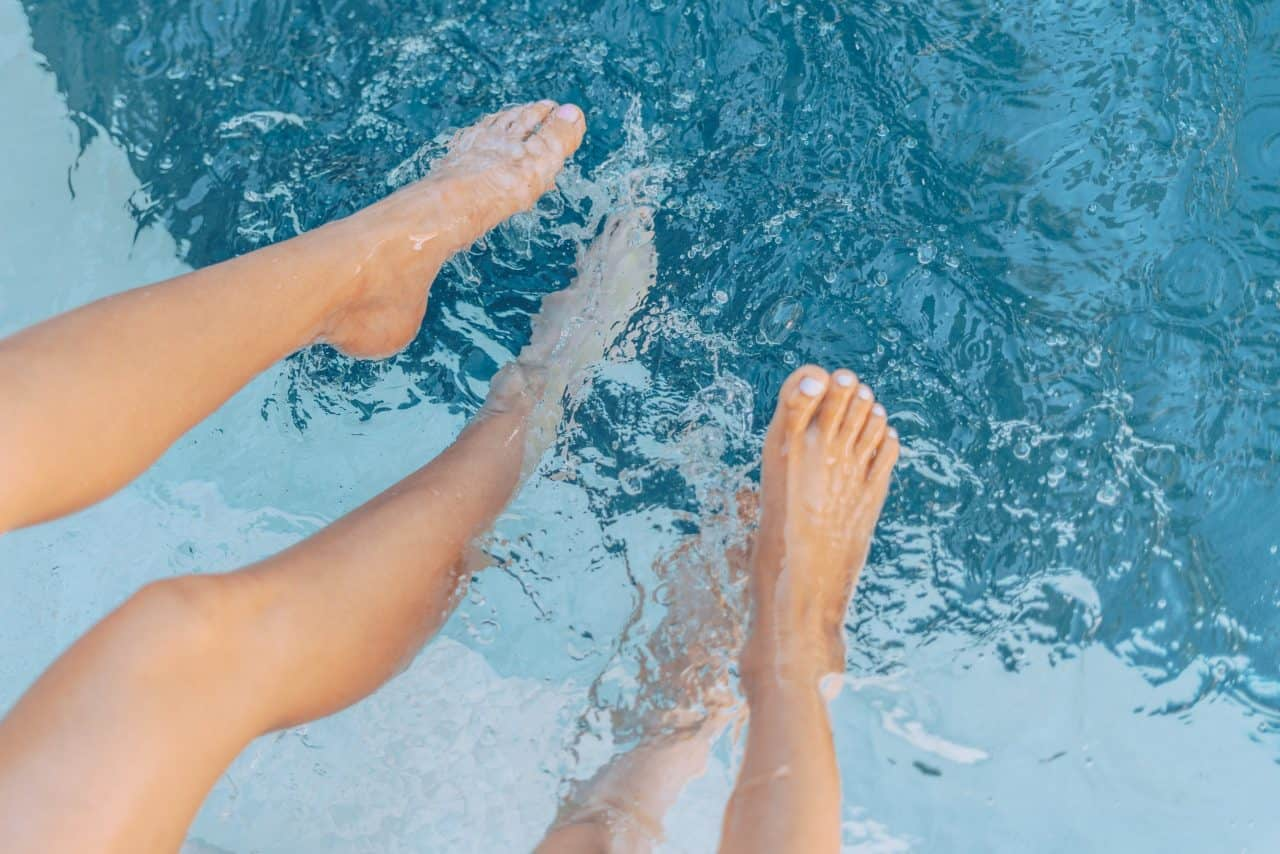feet cooling off in a pool