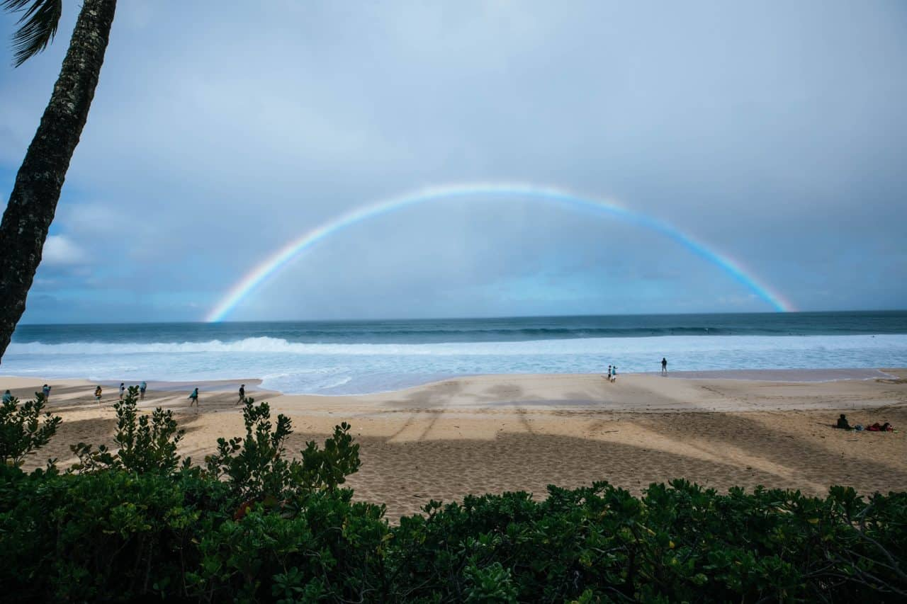 looking at a full rainbow over the ocean from the beach