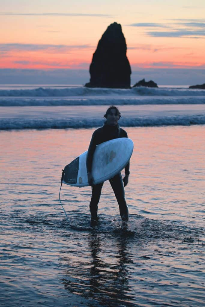 man walking with surfboard out of the ocean at sunset
