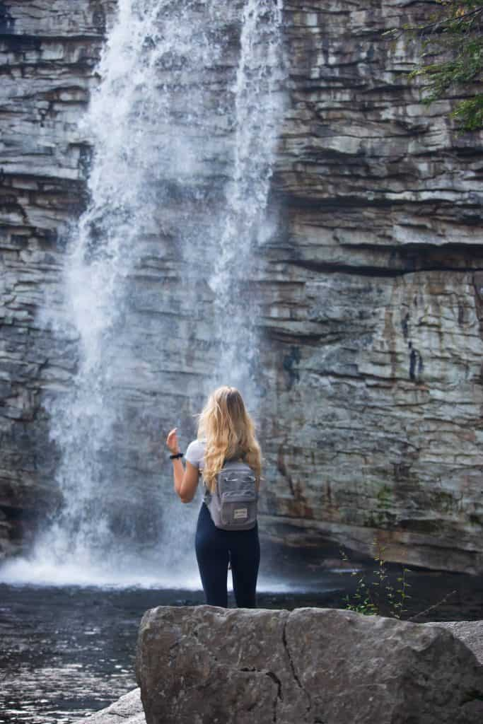 woman at the bottom of a waterfall