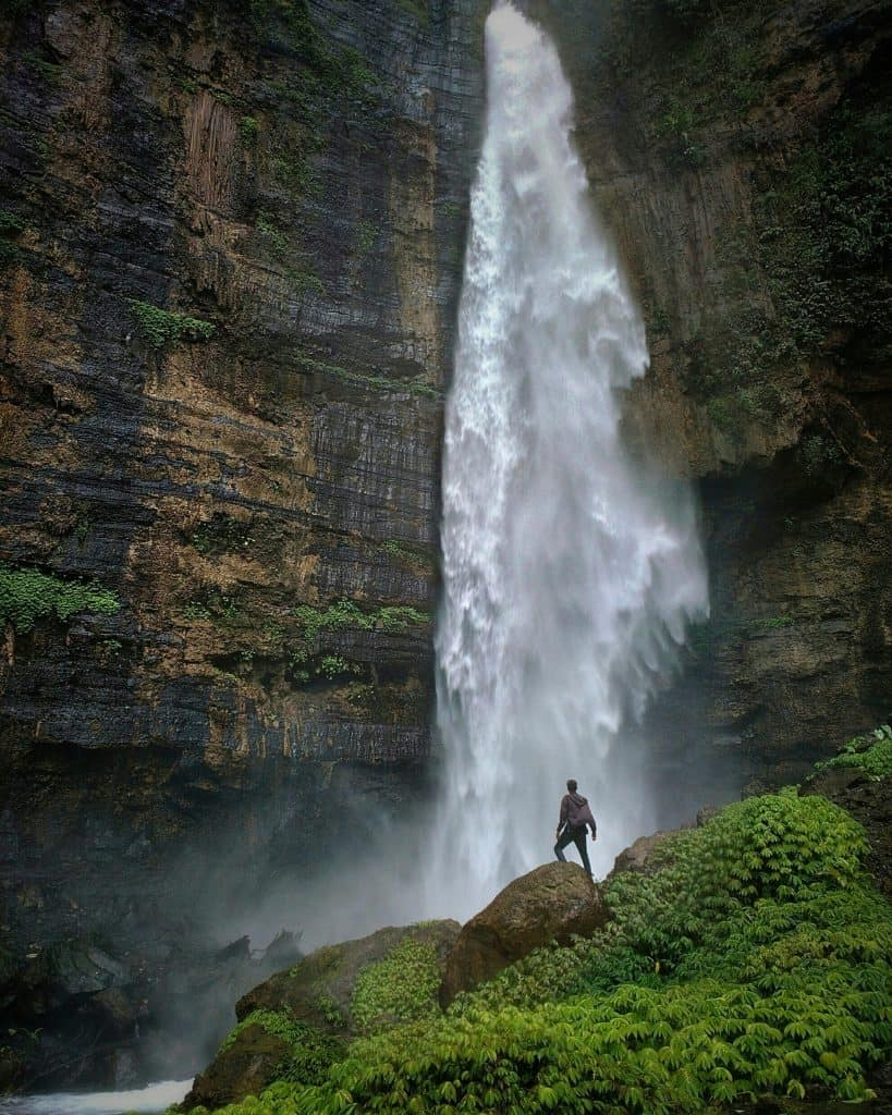 man standing by large waterfall