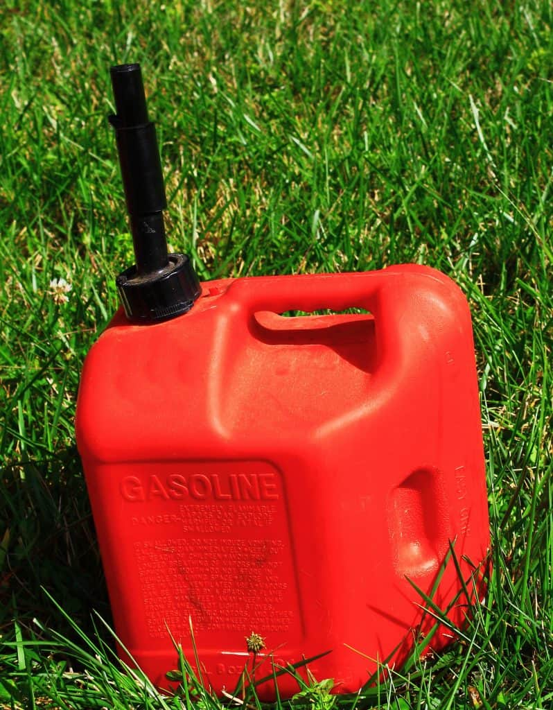 A small red gas can sitting on the grass.