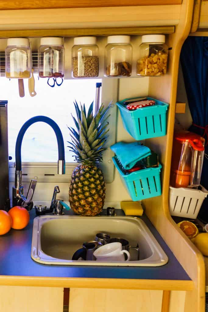 Dishes and a pineapple sitting next to a travel trailer sink.
