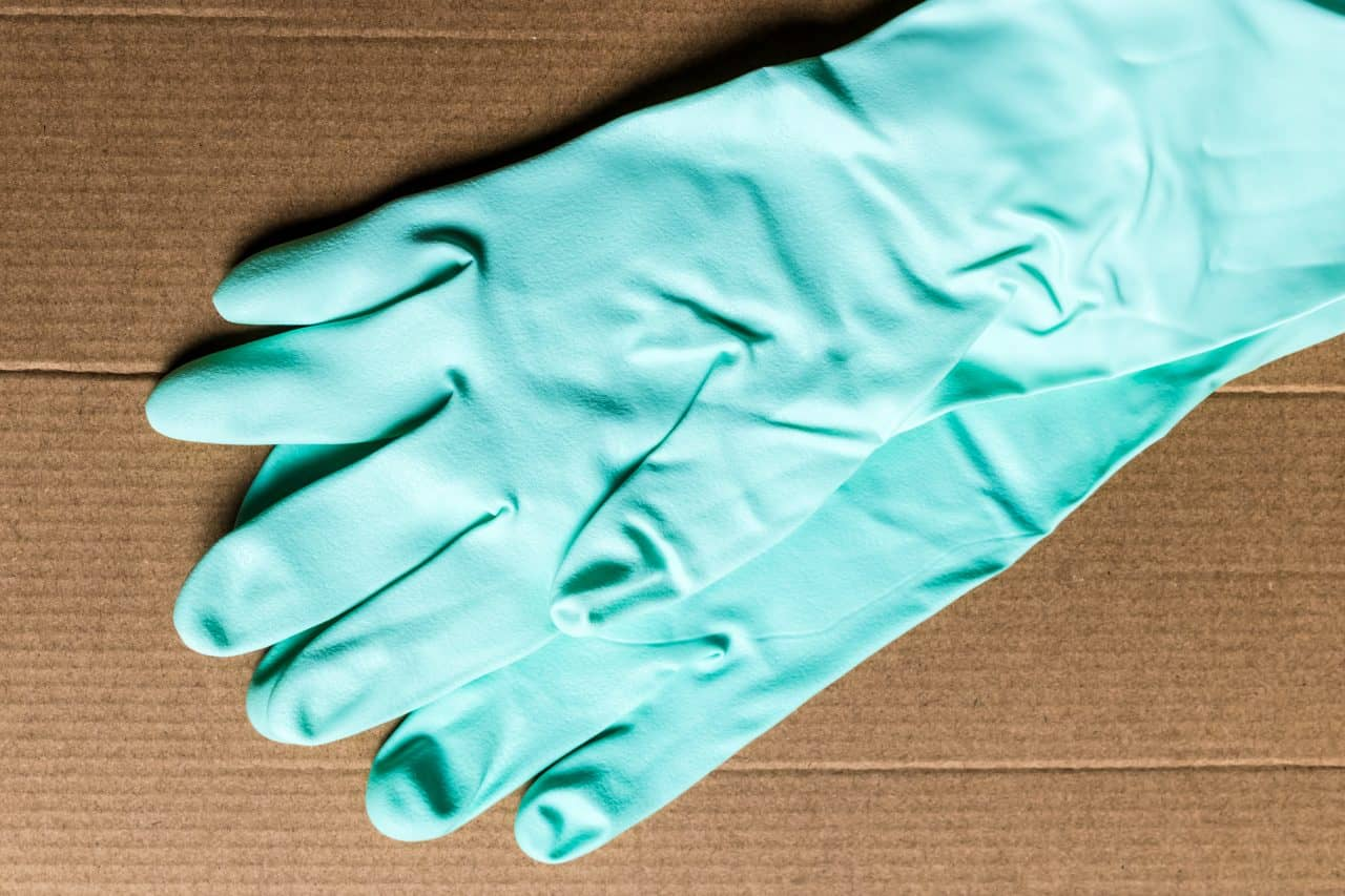 Rubber gloves sitting on piece of cardboard for cleaning travel trailer.