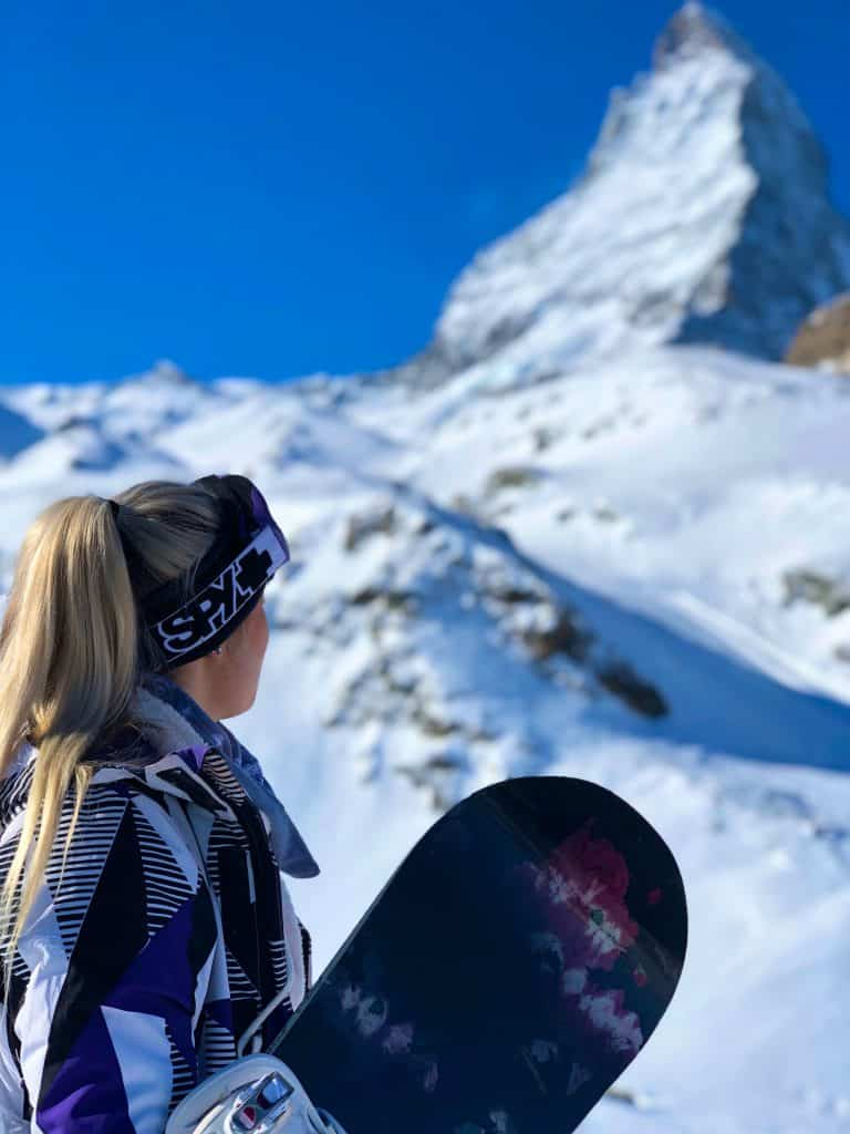 Blonde woman standing in front of a snow covered mountain holding a snowboard.