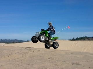 Man jumping a green AVT rental in the Oregon Dunes
