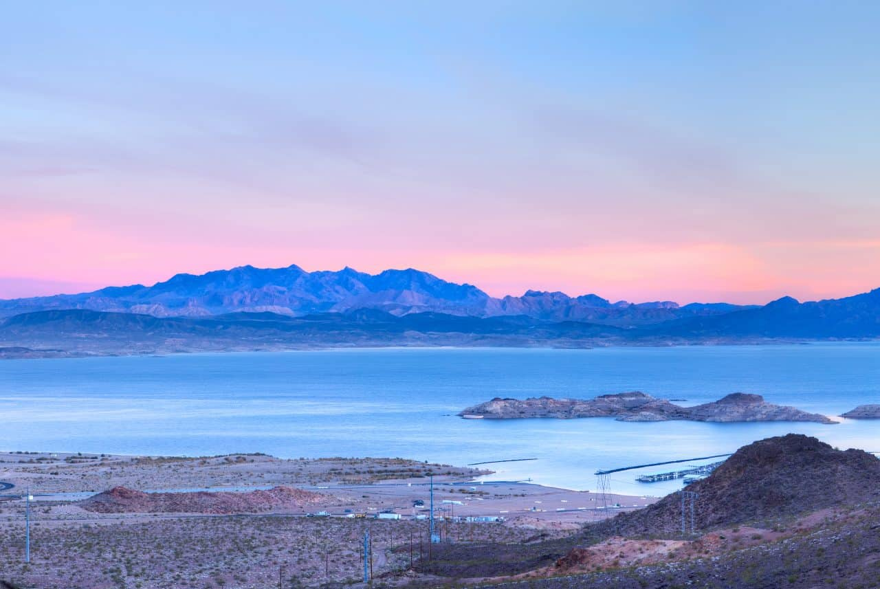 Lake Meade with the mountains and a sunset in the background.