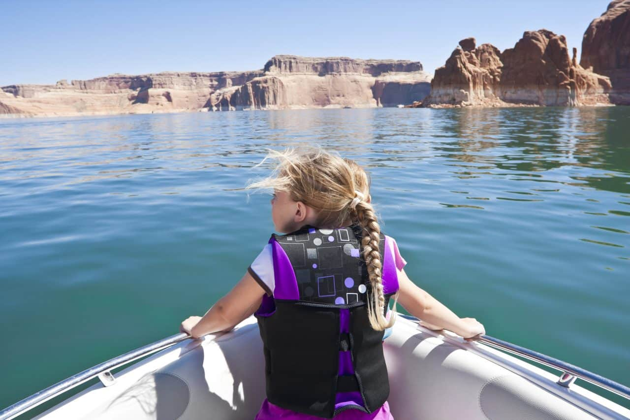 A girl wearing a lifejacket and riding in a ski boat on Lake Powell.