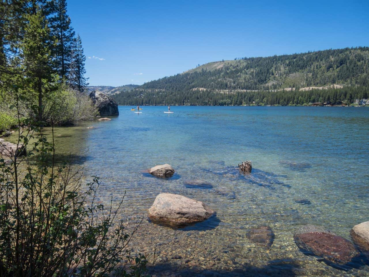 Clear waters of Donner Lake with paddle boarders in the background.