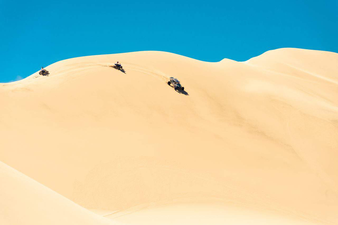 A sand buggy and quads riding a big dune at Dumont Dunes in California.