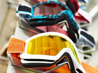 A row of snowboarding goggles displayed on a rack.