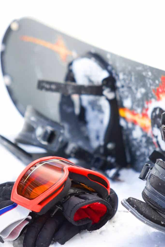 A snowboard, gloves, and snowboarding goggles sitting on the snow.