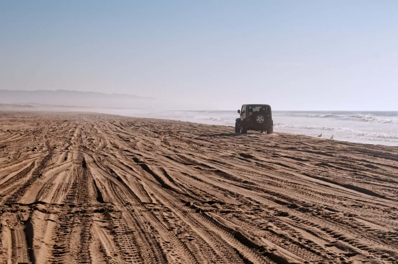 A Jeep driving on the beach at Oceano Sand Dunes a place to ride the Dunes in California.