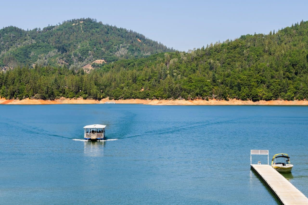 A patio boat driving on Lake Shasta.