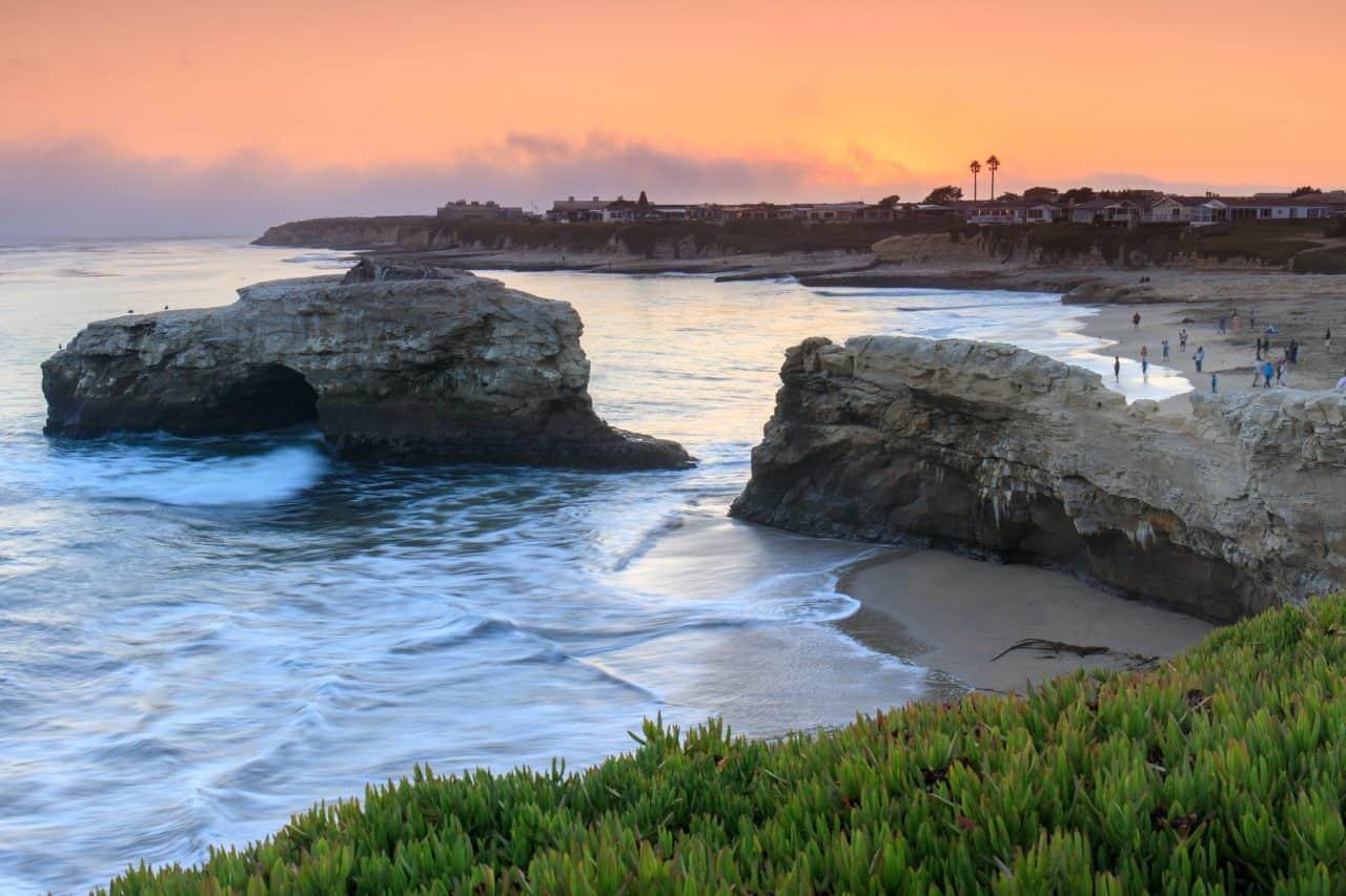 Rocks of Natural Bridges State Beach at sunset.