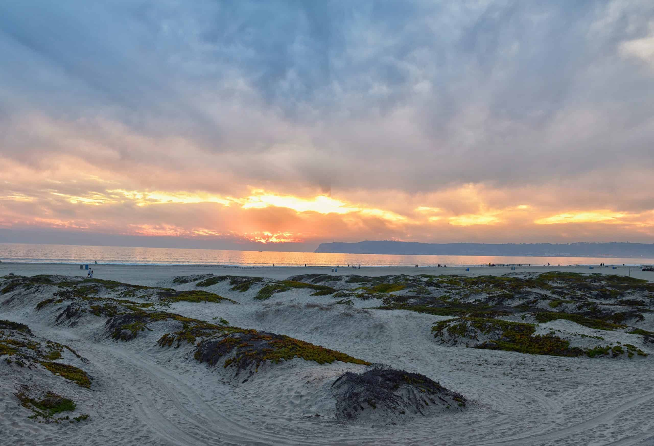 Sunset over the water and sand dunes at Coronado Beach.