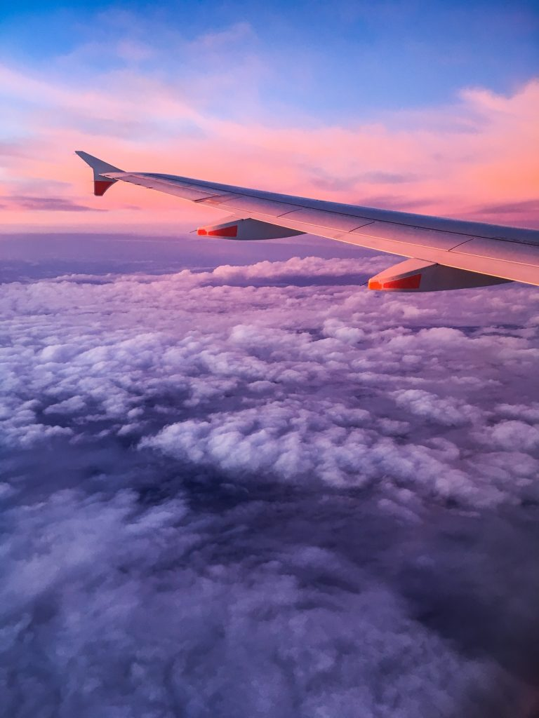 looking out window of plane at sunset