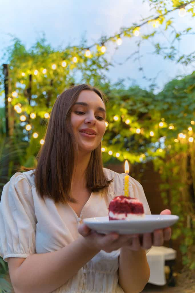 woman holding a birthday cake with candle