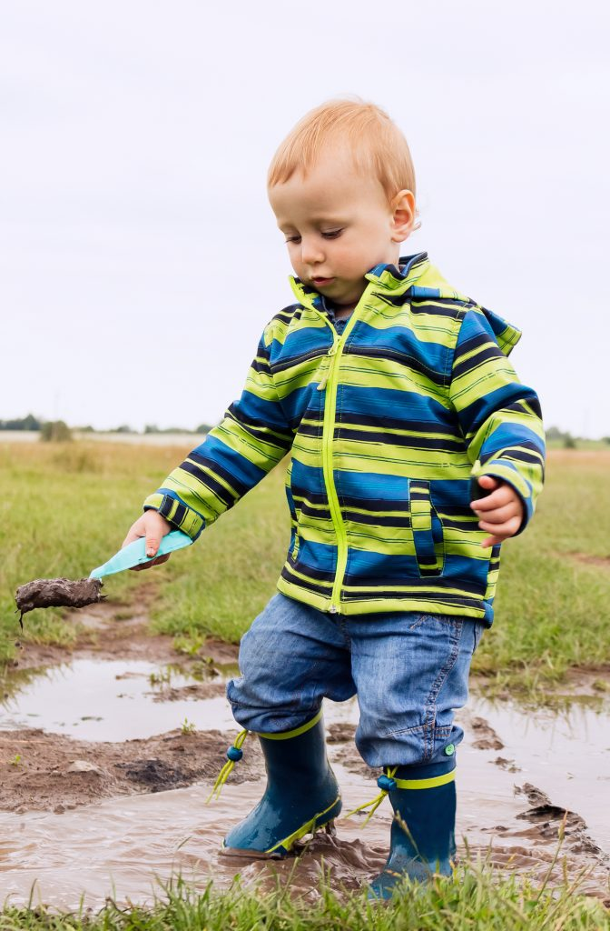 a boy playing in the mud