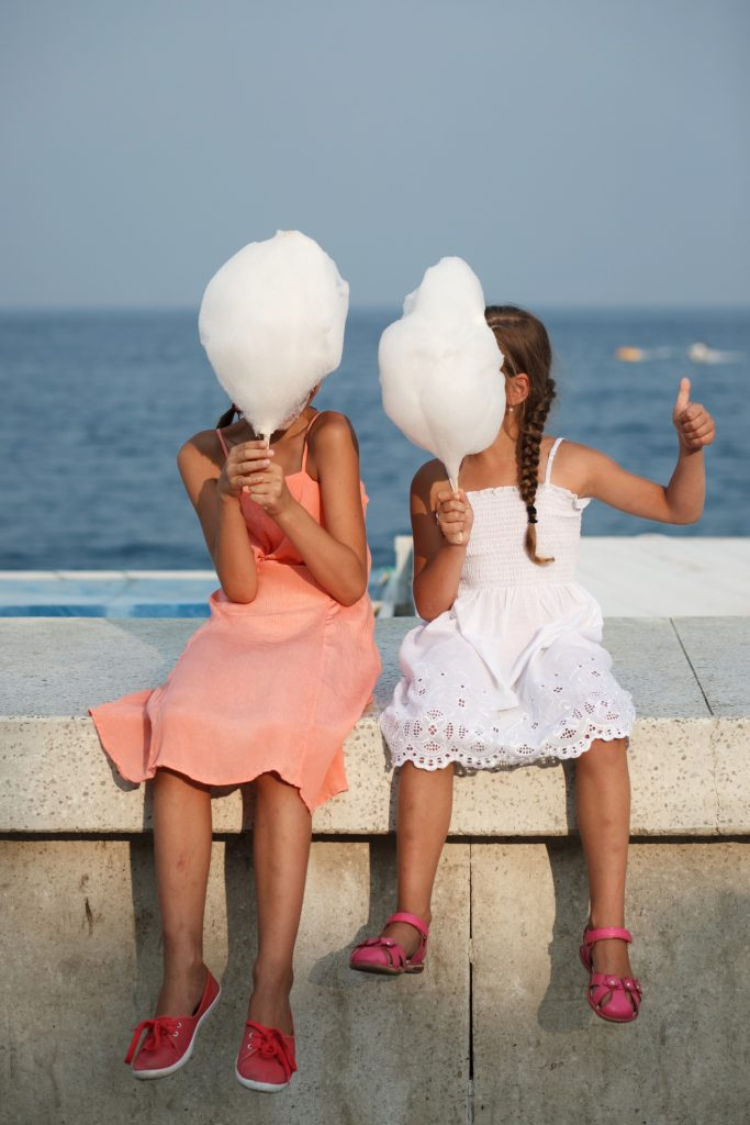 girls holding cotton candy at the beach