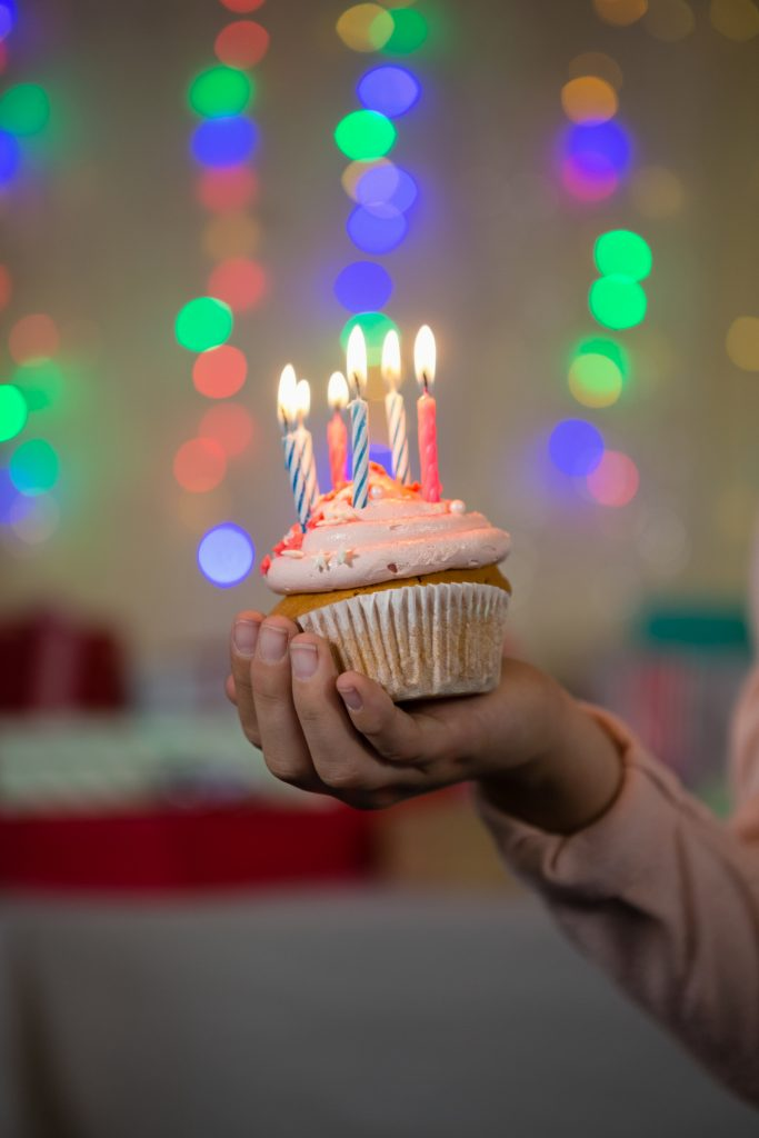 someone holding a cupcake with candles