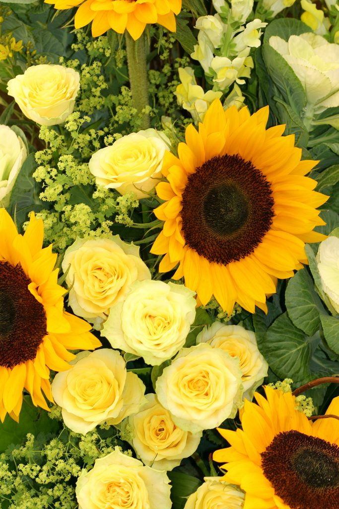 arrangement of sunflowers and yellow roses