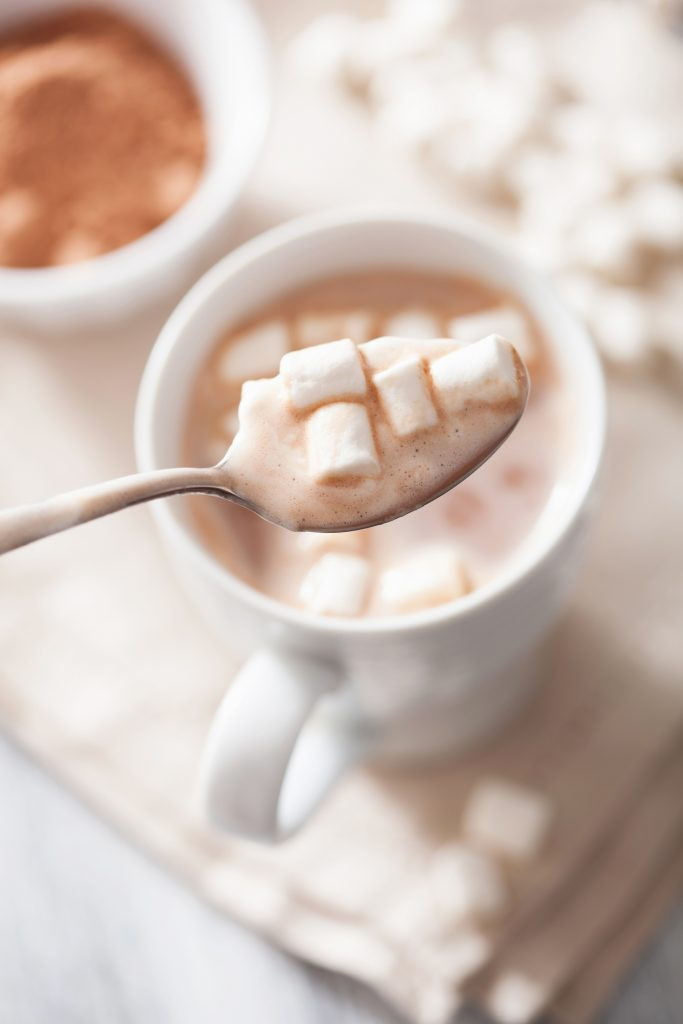 spoon holding marshmallows over hot cocoa