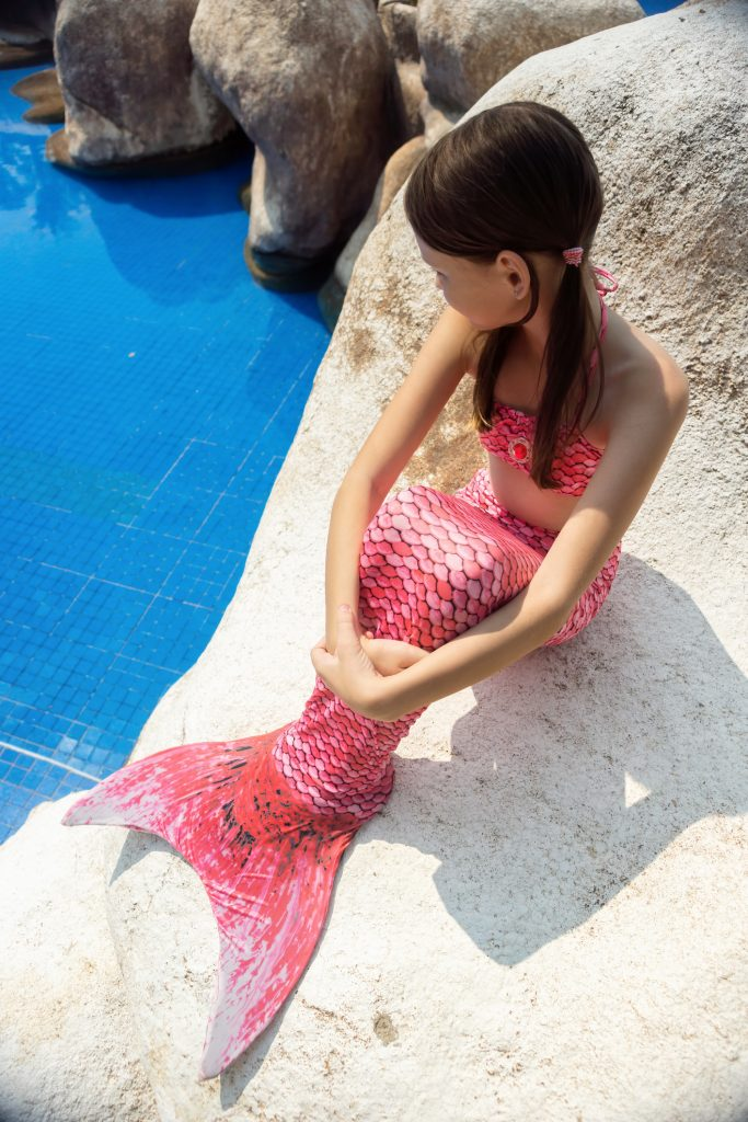 girl sitting next to pool in a fin