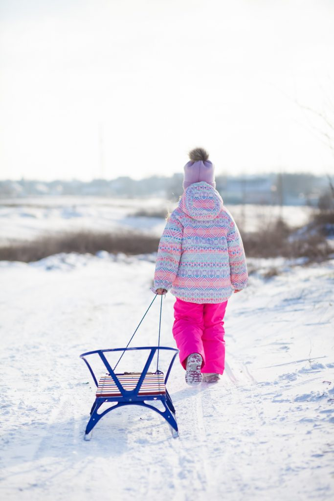 child pulling sled in snow
