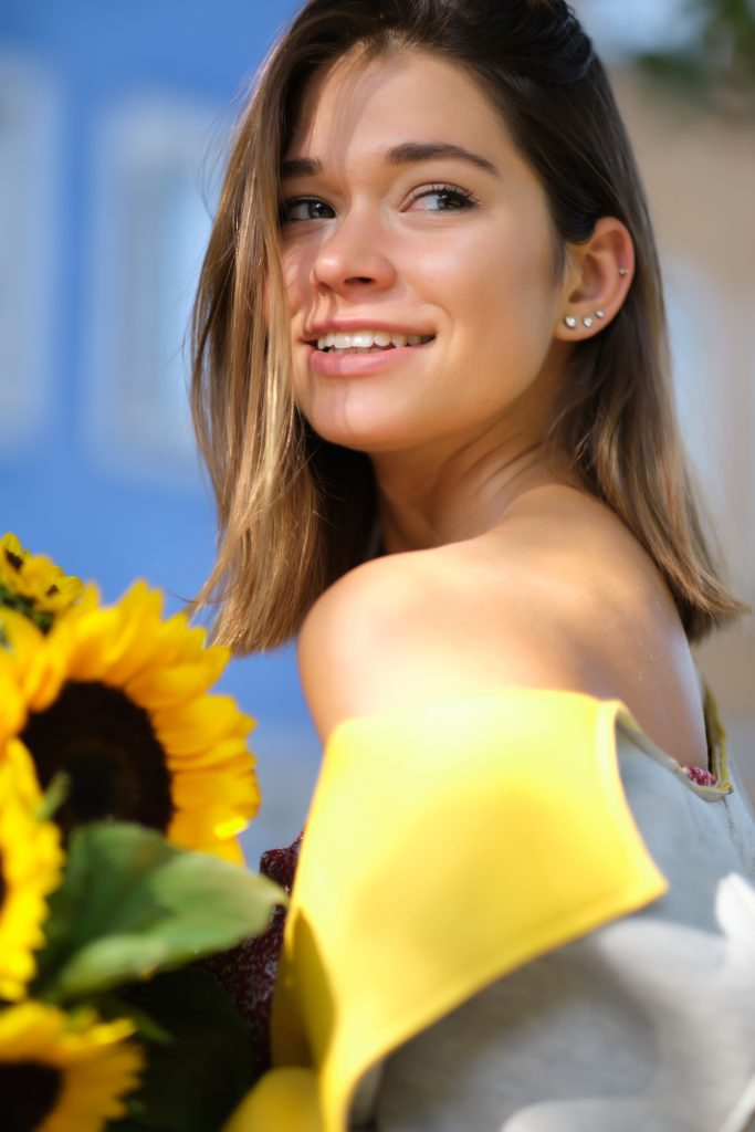smiling woman with sunflowers